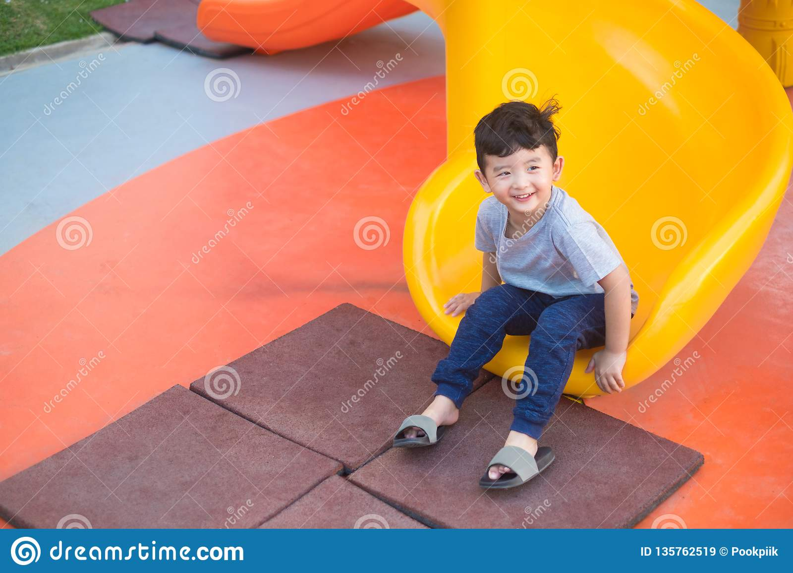 Asian kid playing slide at the playground under the sunlight in summer, Happy kid in kindergarten or preschool school yard