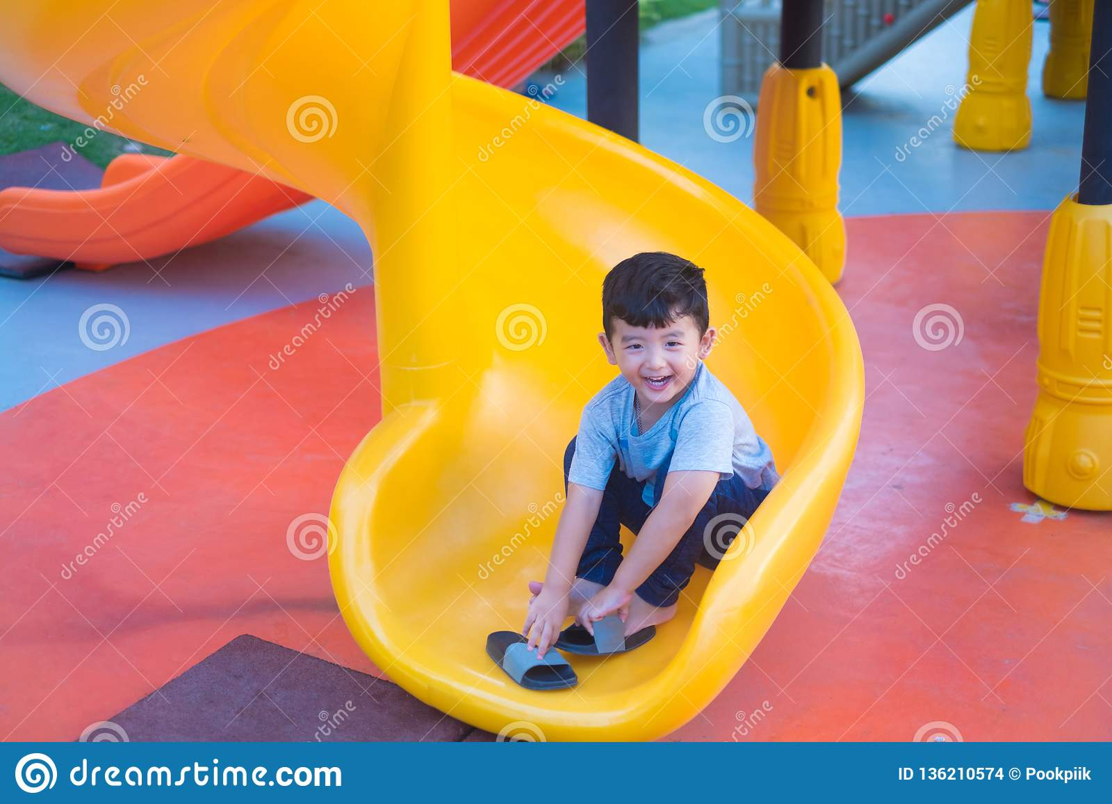 Asian kid playing slide at the playground under the sunlight in summer, Happy kid in kindergarten or preschool school yard