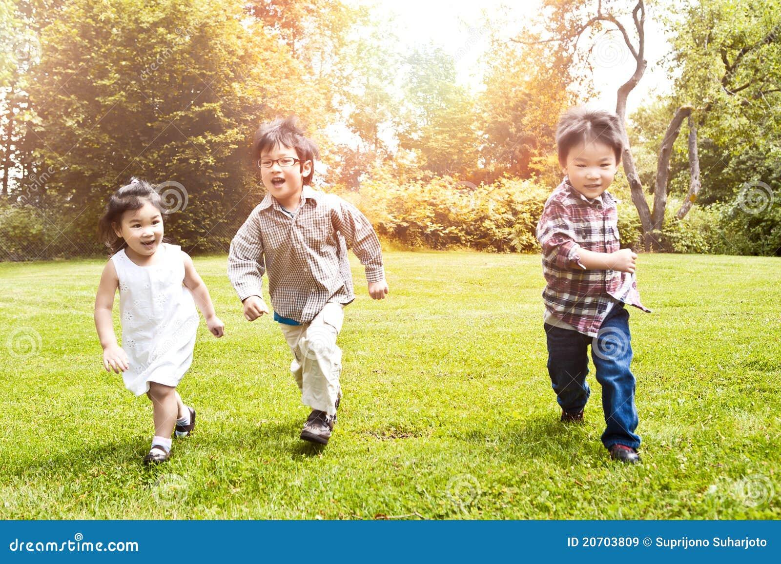 Asian kids running in park