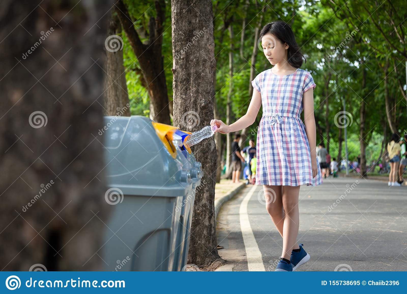 Asian little child girl hand holding plastic bottle,putting plastic water bottle in recycling bin,tourist woman hand throwing