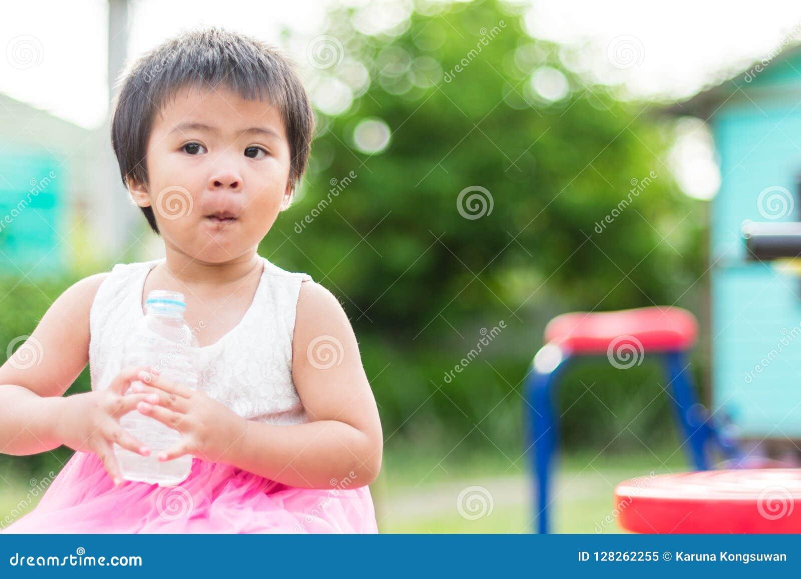 Asian little cute girl drinking clean water from plastic bottle