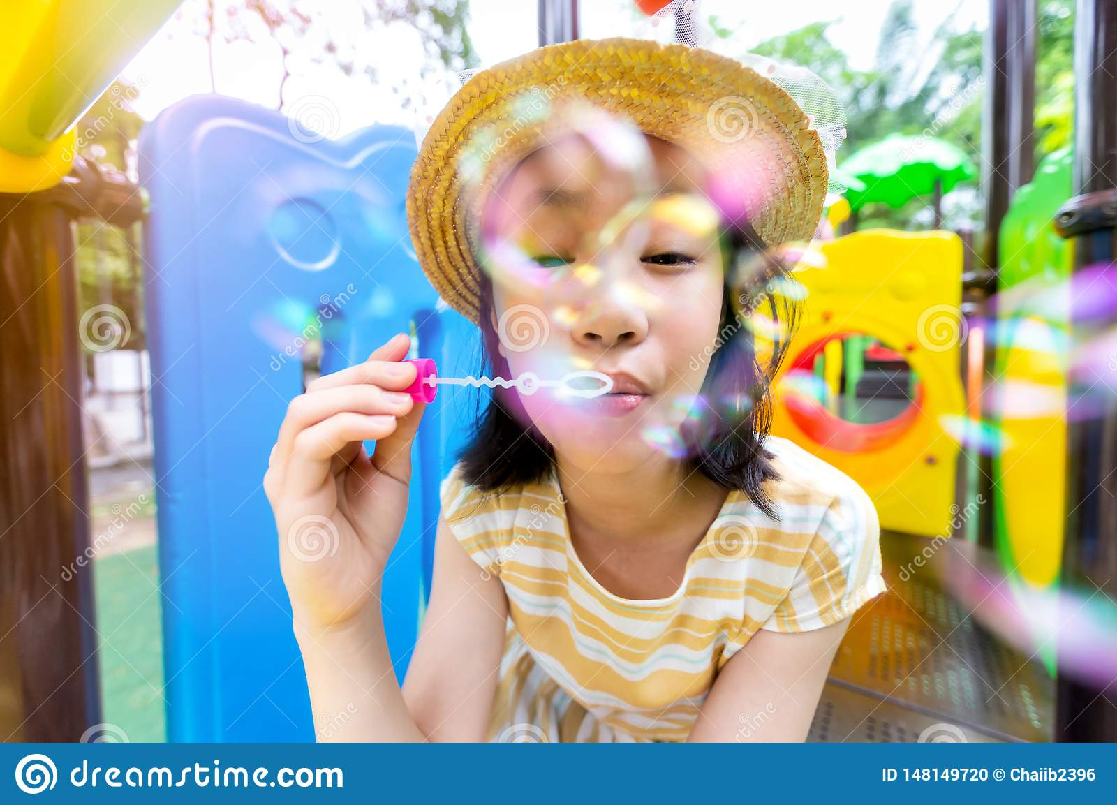Asian Little Girl Blowing Bubbles On A Playground Outdoor