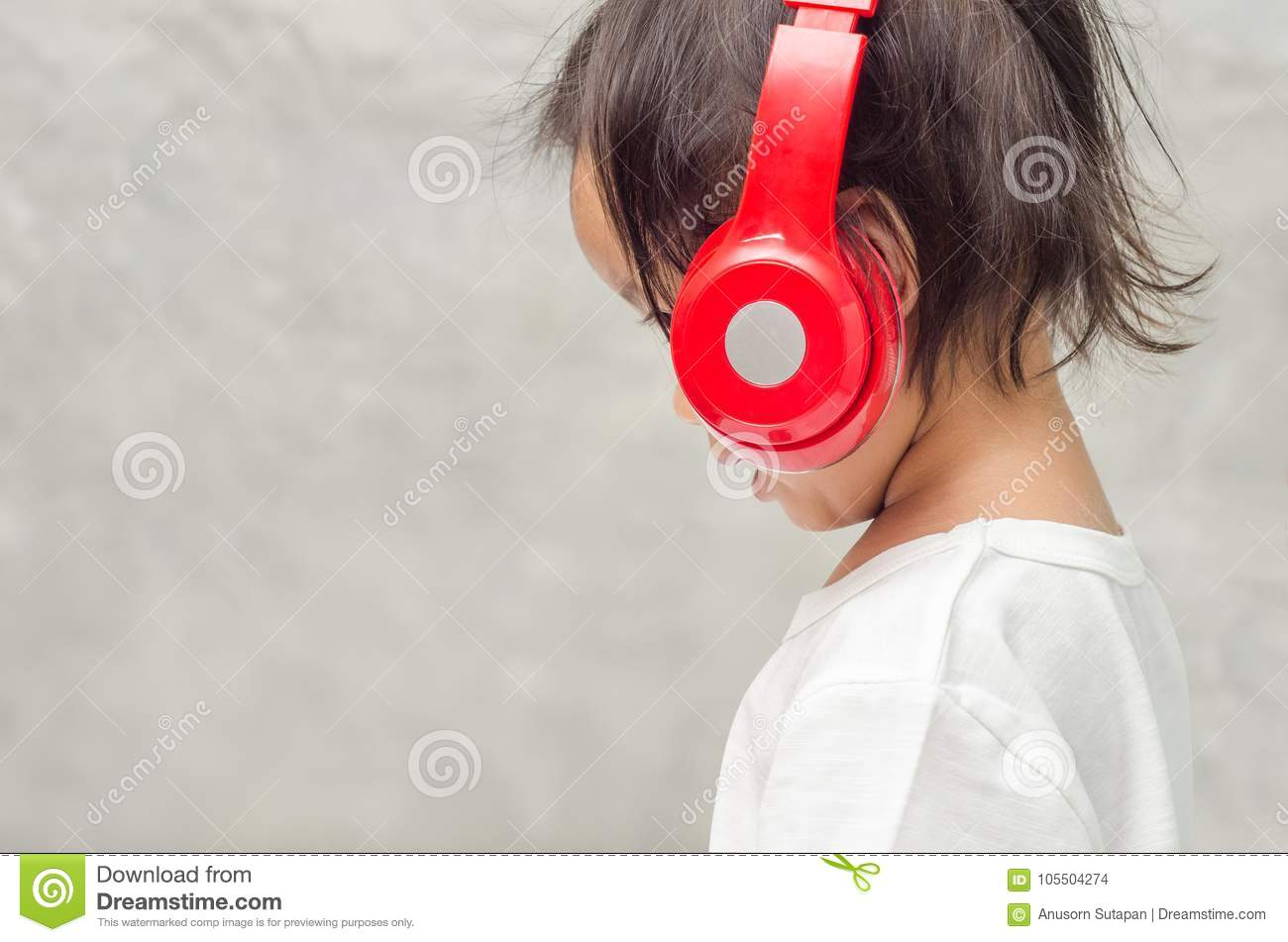 Asian little girl with headphones in the bedroom at home