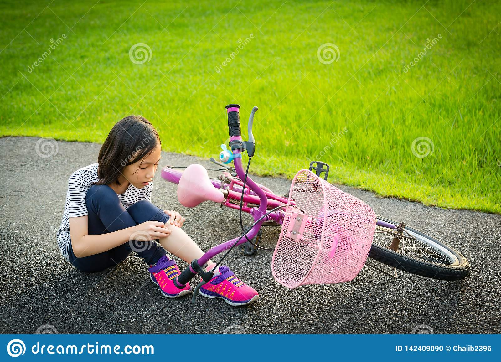 Asian little girl sitting down on the road with a leg pain due to a bicycle accident,the bike fall near the child,girl riding a