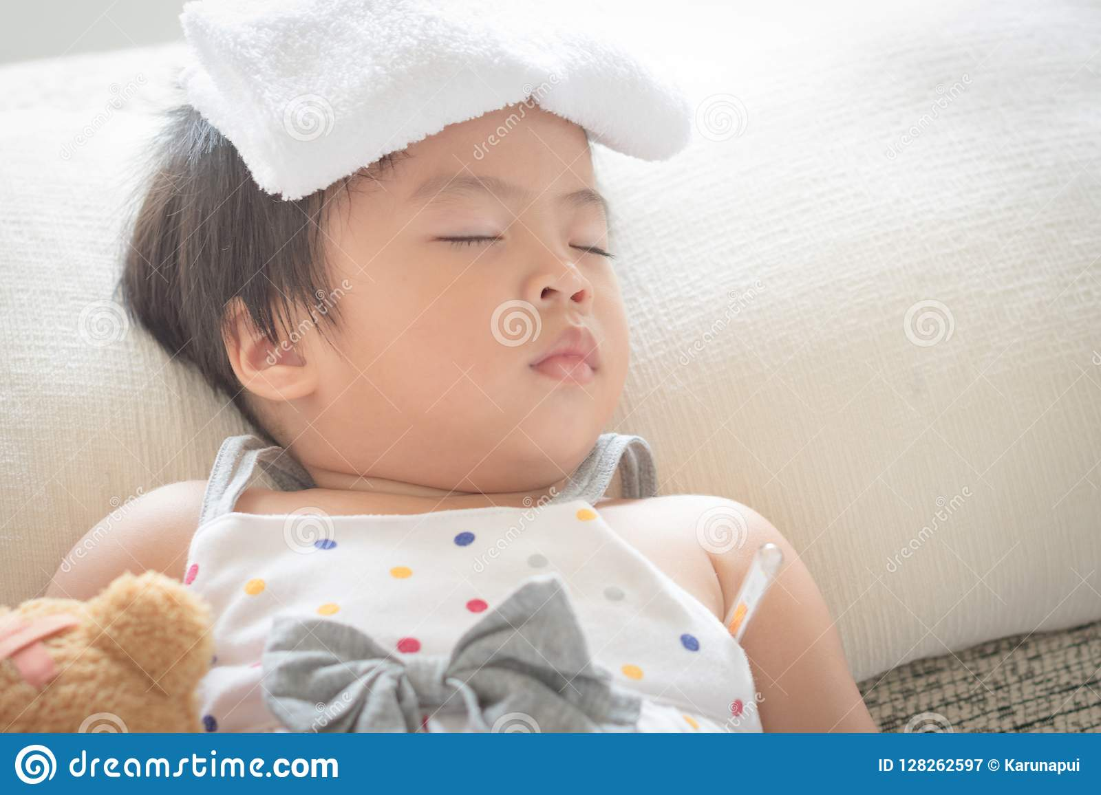 Asian little girl sleep and sick on sofa with cooler gel on her