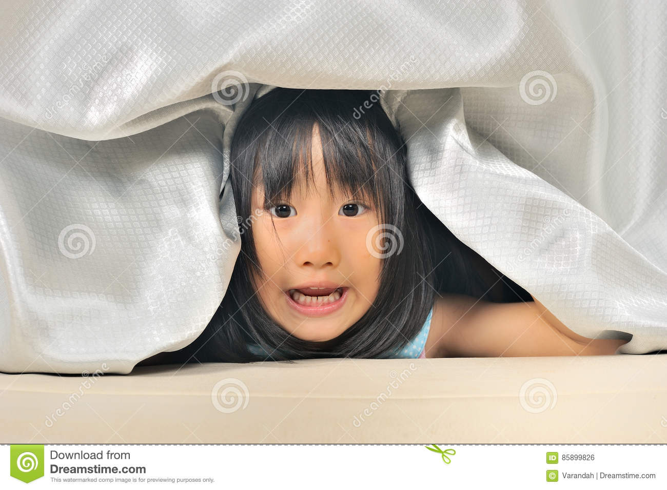 Asian Little kid playing and peeking out from a curtain