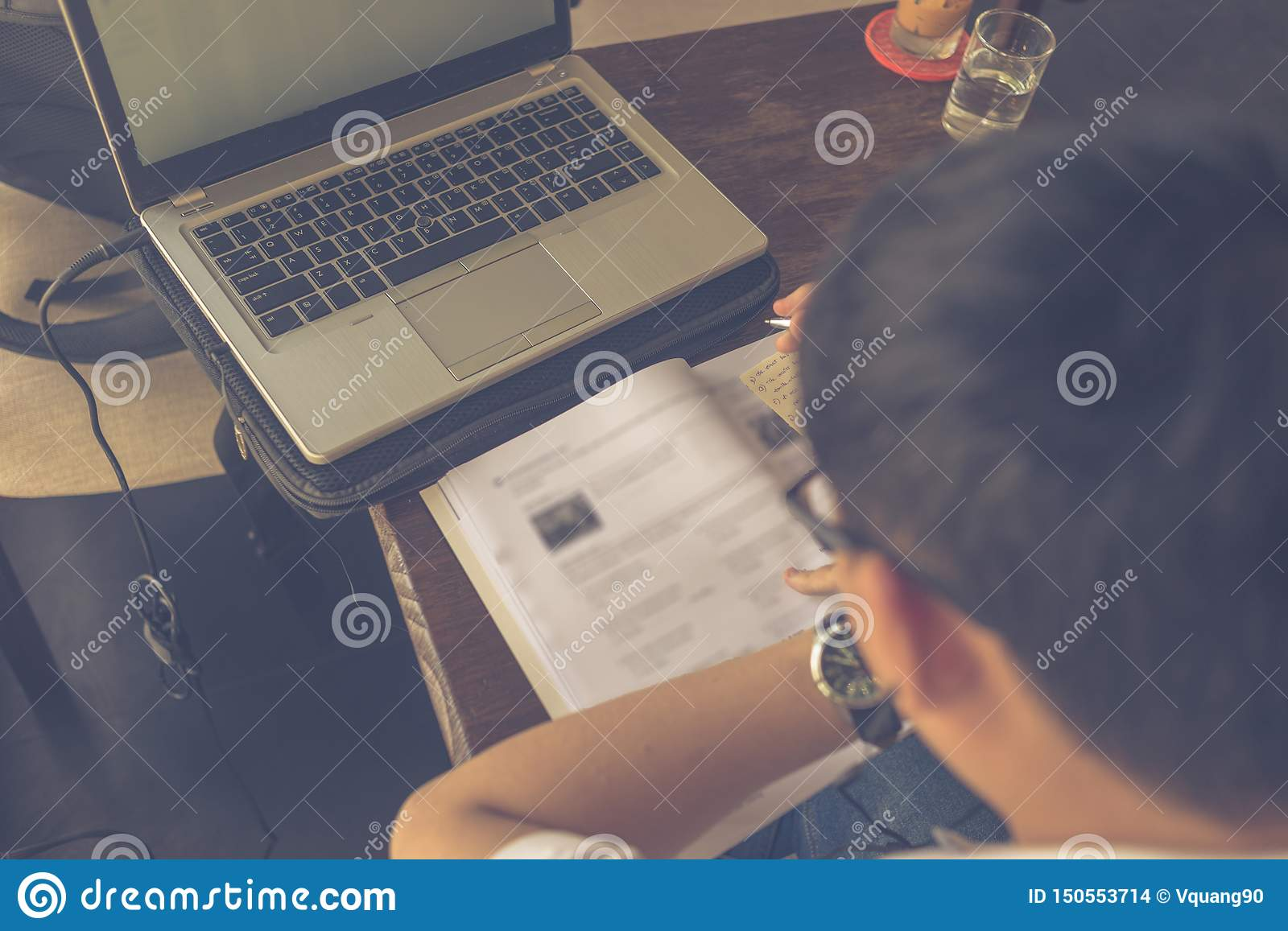 Rear view of Asian studying English with laptop and workbook