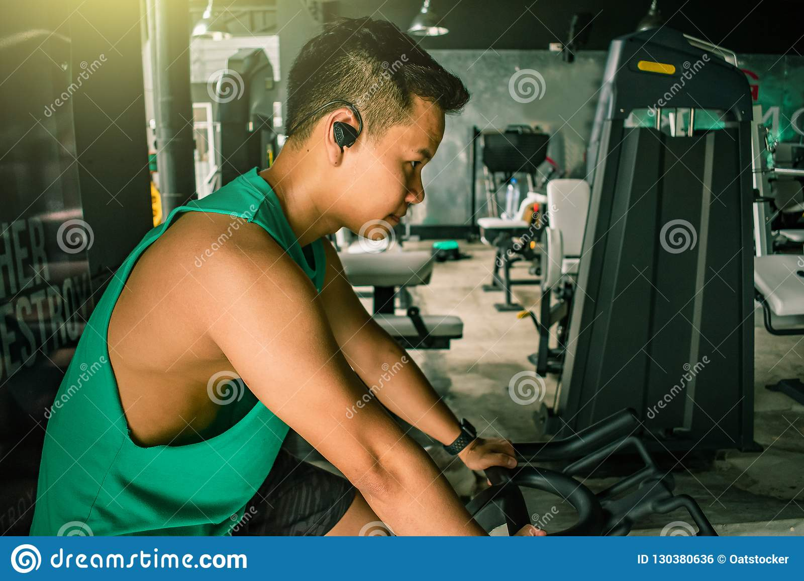 Asian man Bodybuilder with bicycle machine weights power handsome