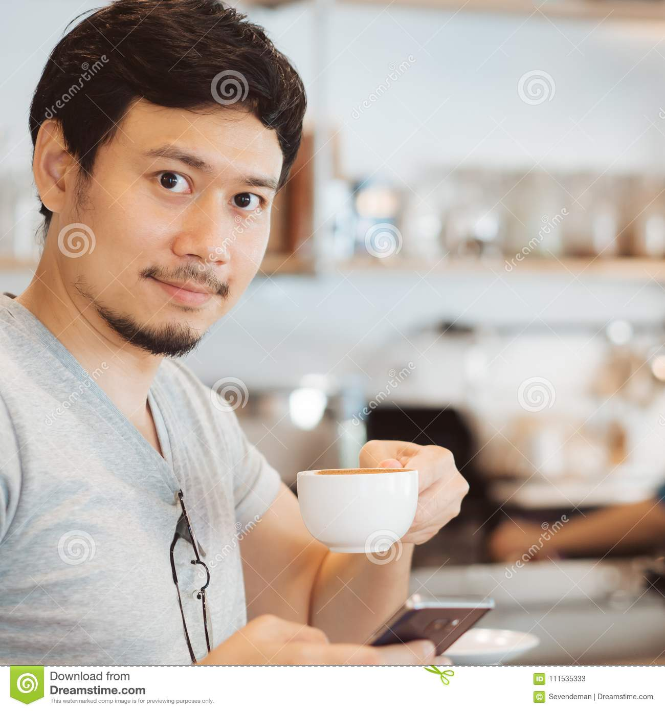 Man is drinking hot coffee in the coffee cafe.