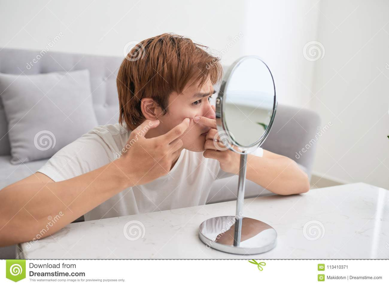Asian man looking at mirror and popping a pimple