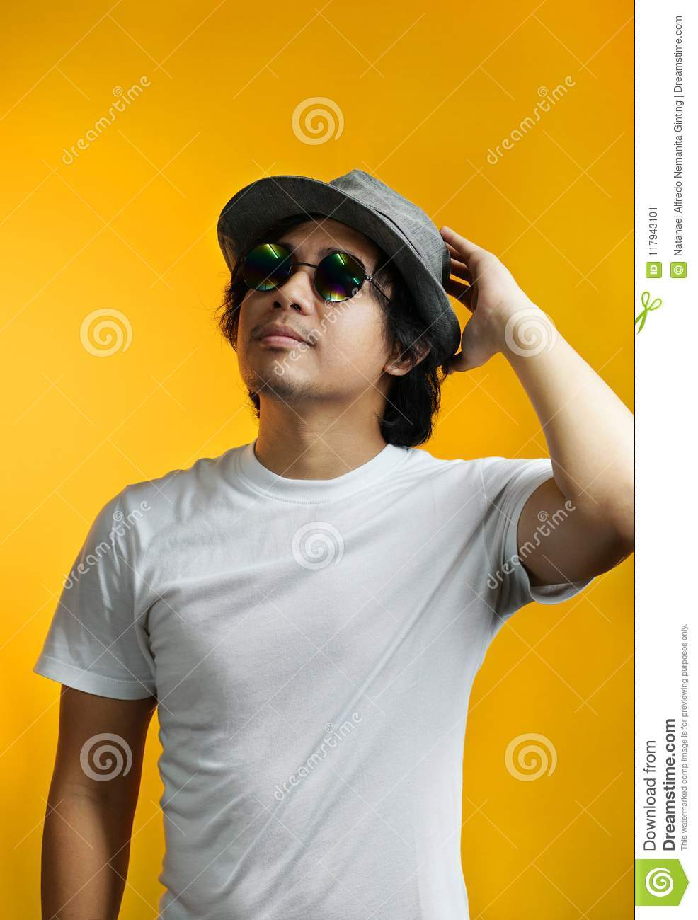 Asian Man Looking up and Holding His Head Wearing Sunglasses and
