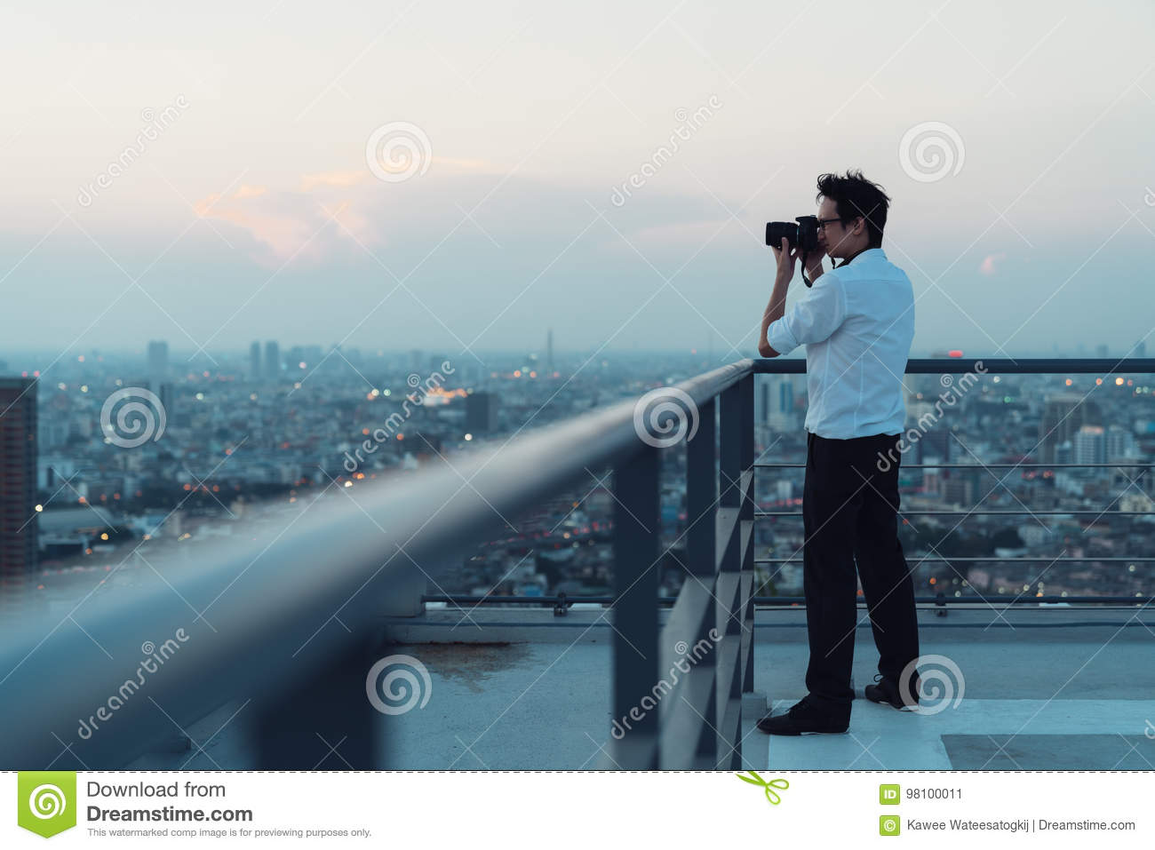 Download Asian Man Taking Cityscape Photo On Building Rooftop In Low Light Situation. Photography & Asian Man Taking Cityscape Photo On Building Rooftop In Low Light ...