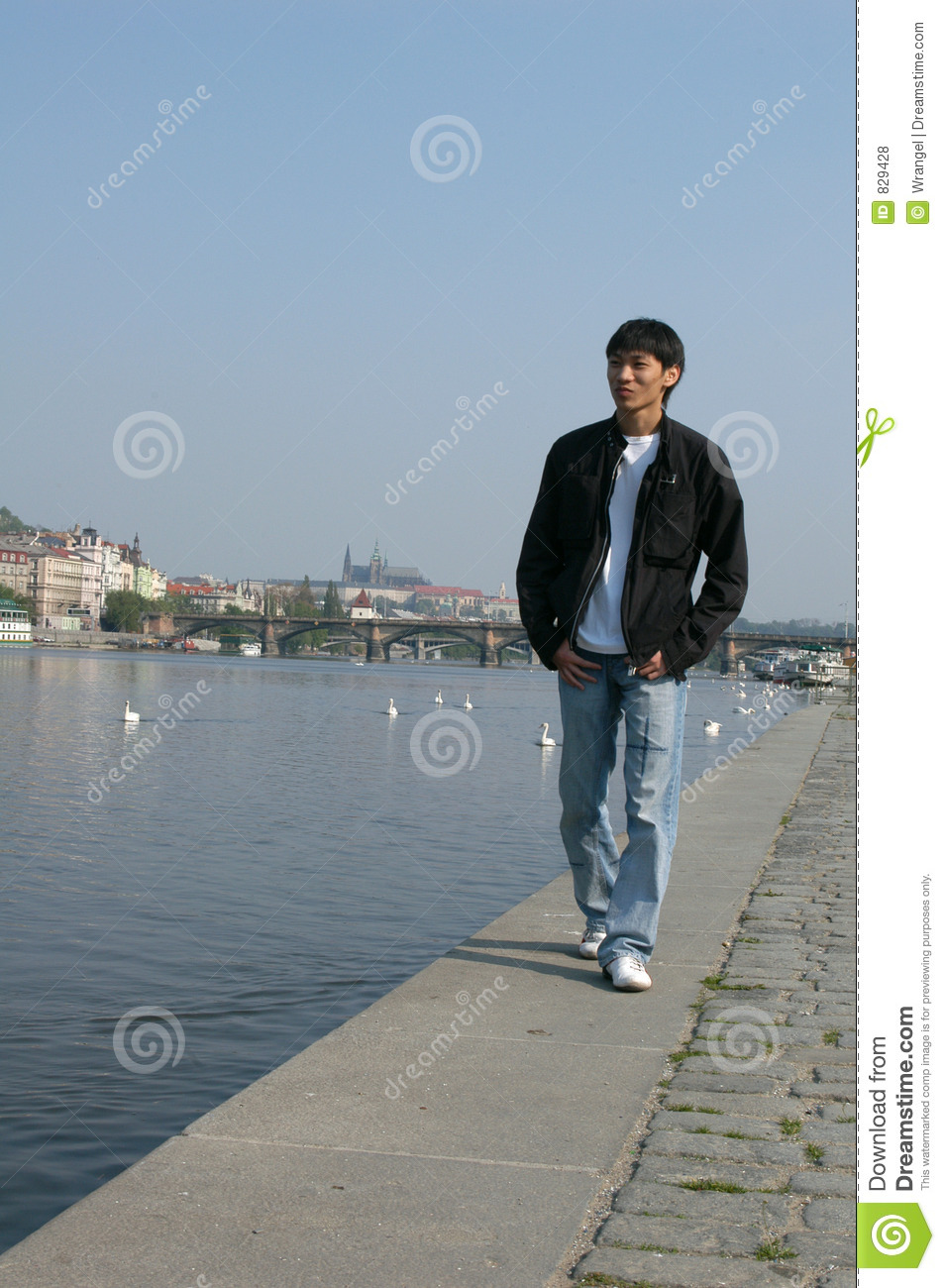 Asian Man Walking along the Embankment