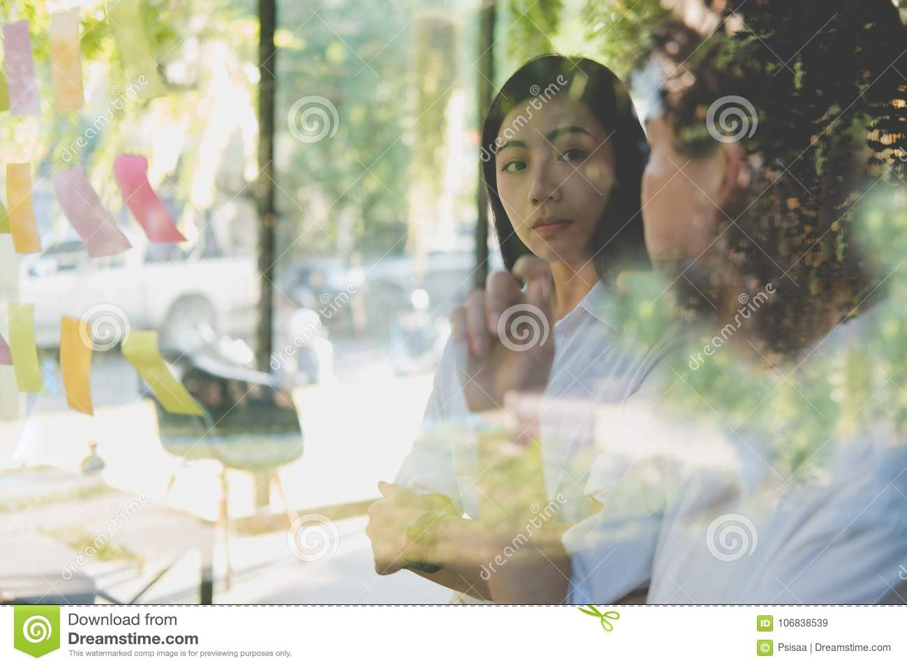 man & woman discussing creative idea with adhesive notes on glass wall at workplace. Sticky note paper reminder schedule
