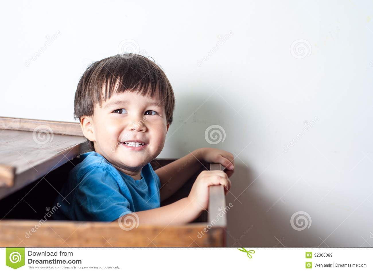 Asian, mixed race boy playing hide and seek in a ooden toy box