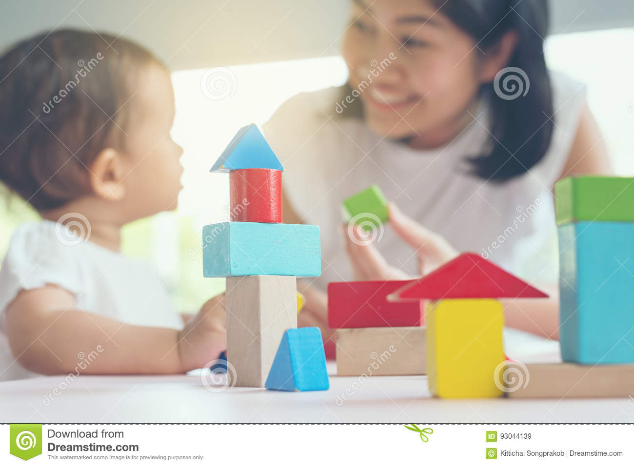 Asian mom and girl kid playing with blocks. Selective focus and