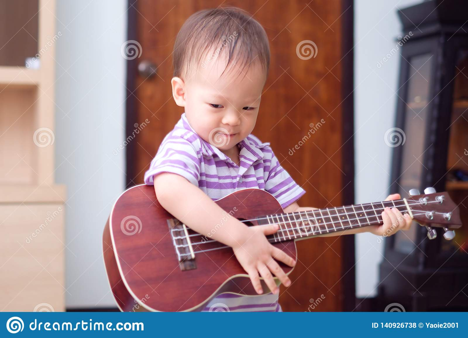 Asian 18 months / 1 year old baby boy child hold & play Hawaiian guitar or ukulele