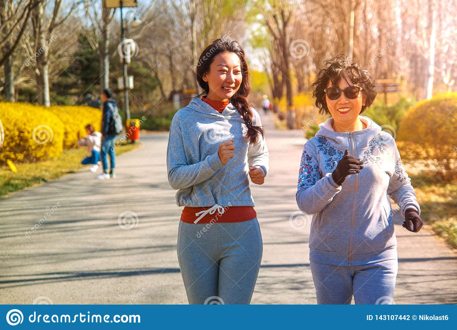 Mother and adult daughter running for sport in park for better fitness.