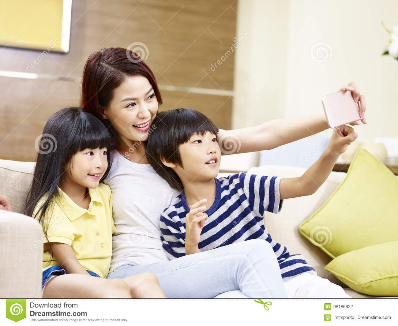 Asian Mother And Children Taking A Selfie At Home Stock Photo