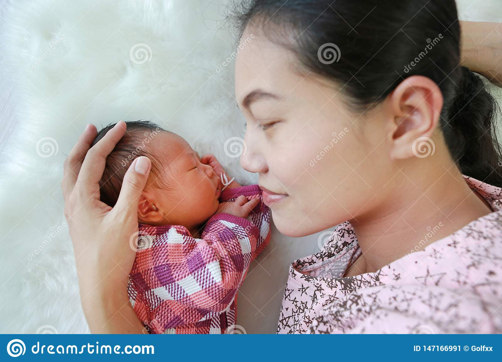 Asian mother lying with her son on white fur background. Close-up of baby and mom