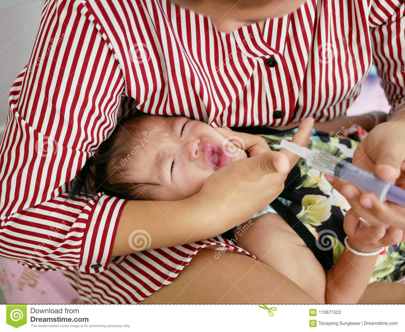Asian mother`s arm wrapping around her crying baby girl`s face forcing the baby to take liquid medicine