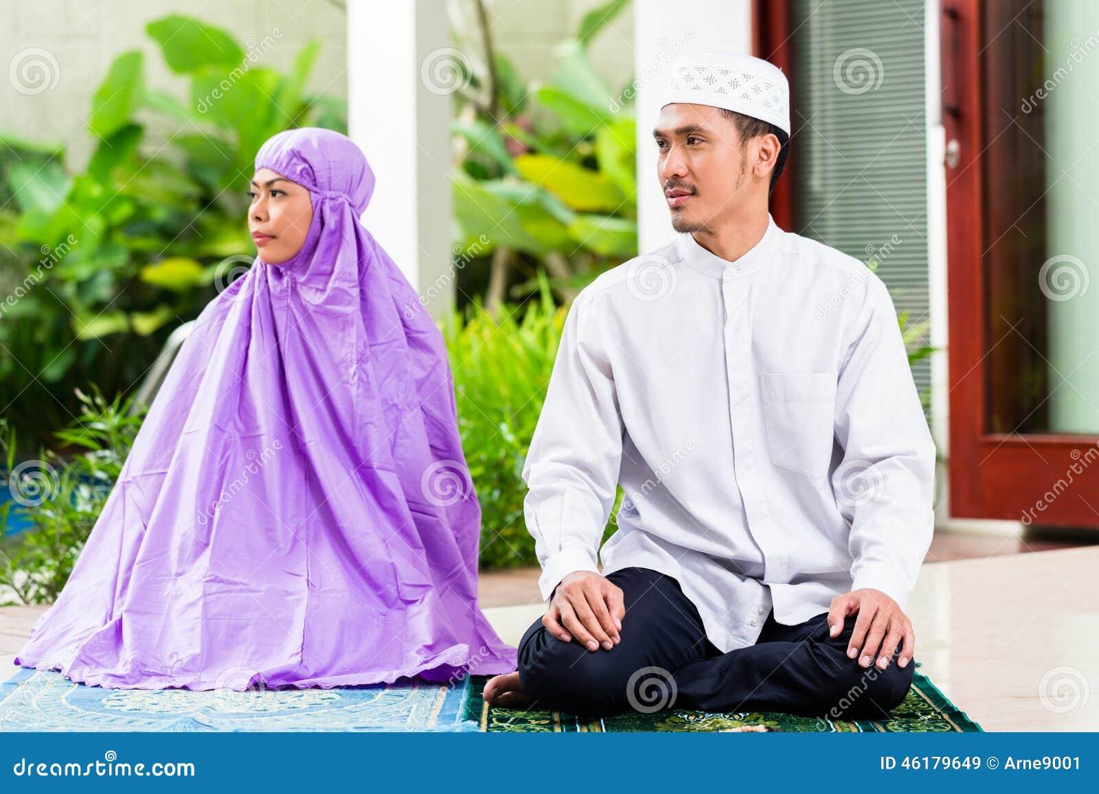 Asian Muslim Couple, Man And Woman, Praying At Home Stock ...