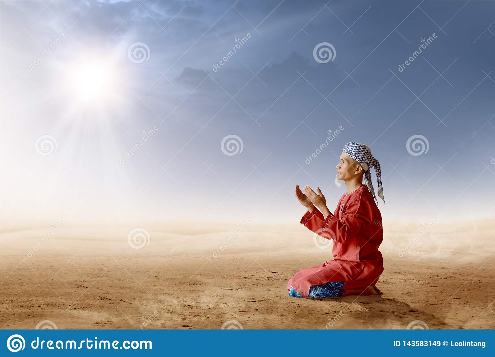 Asian muslim man with turban in his head kneeling and praying with raised hands on desert