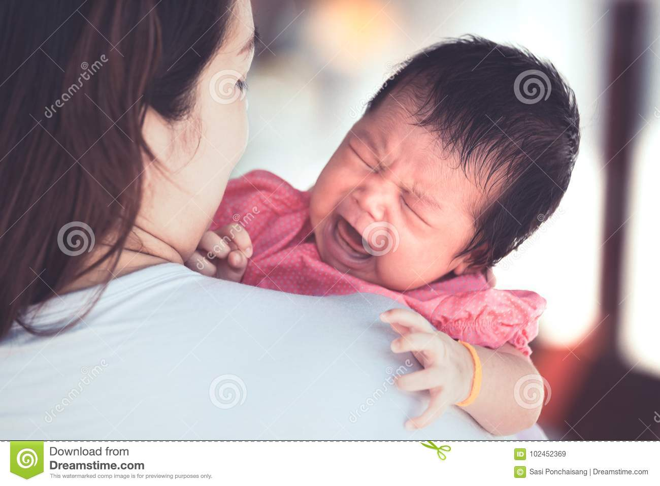 Asian newborn baby girl crying with tried on mother`s shoulder