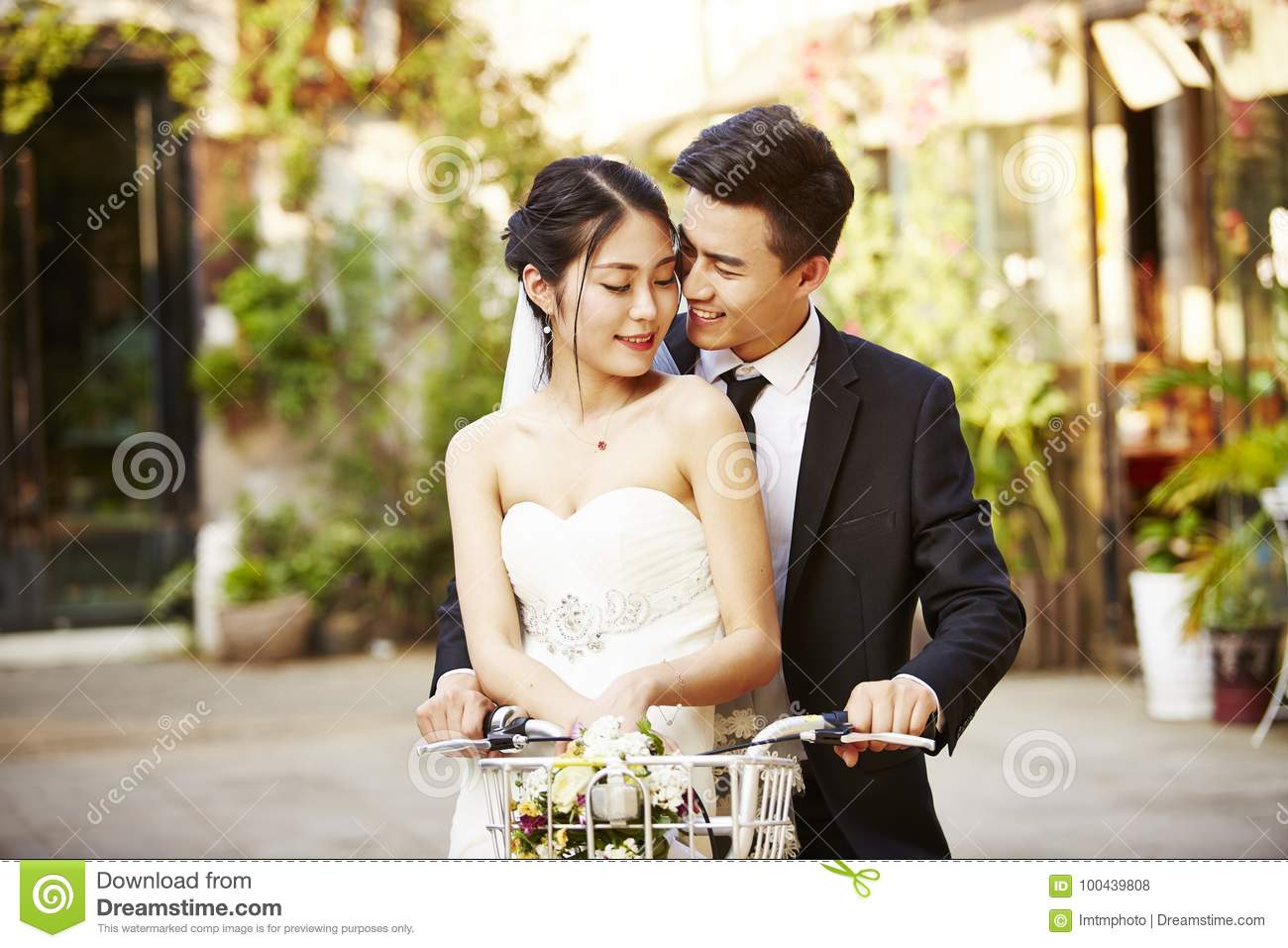 Asian newly wed couple riding a bicycle