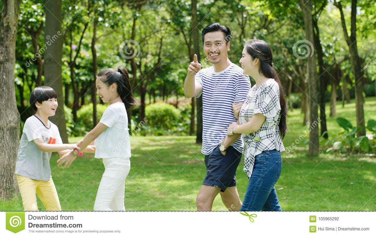 Asian family playing & laughing outdoors in park in summer