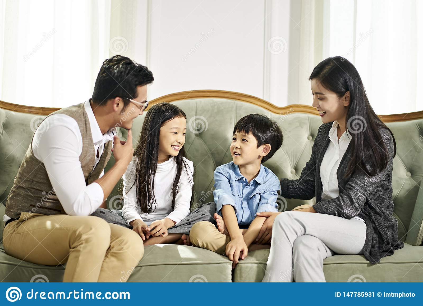 Asian Parents And Two Children Chatting At Home Stock ...