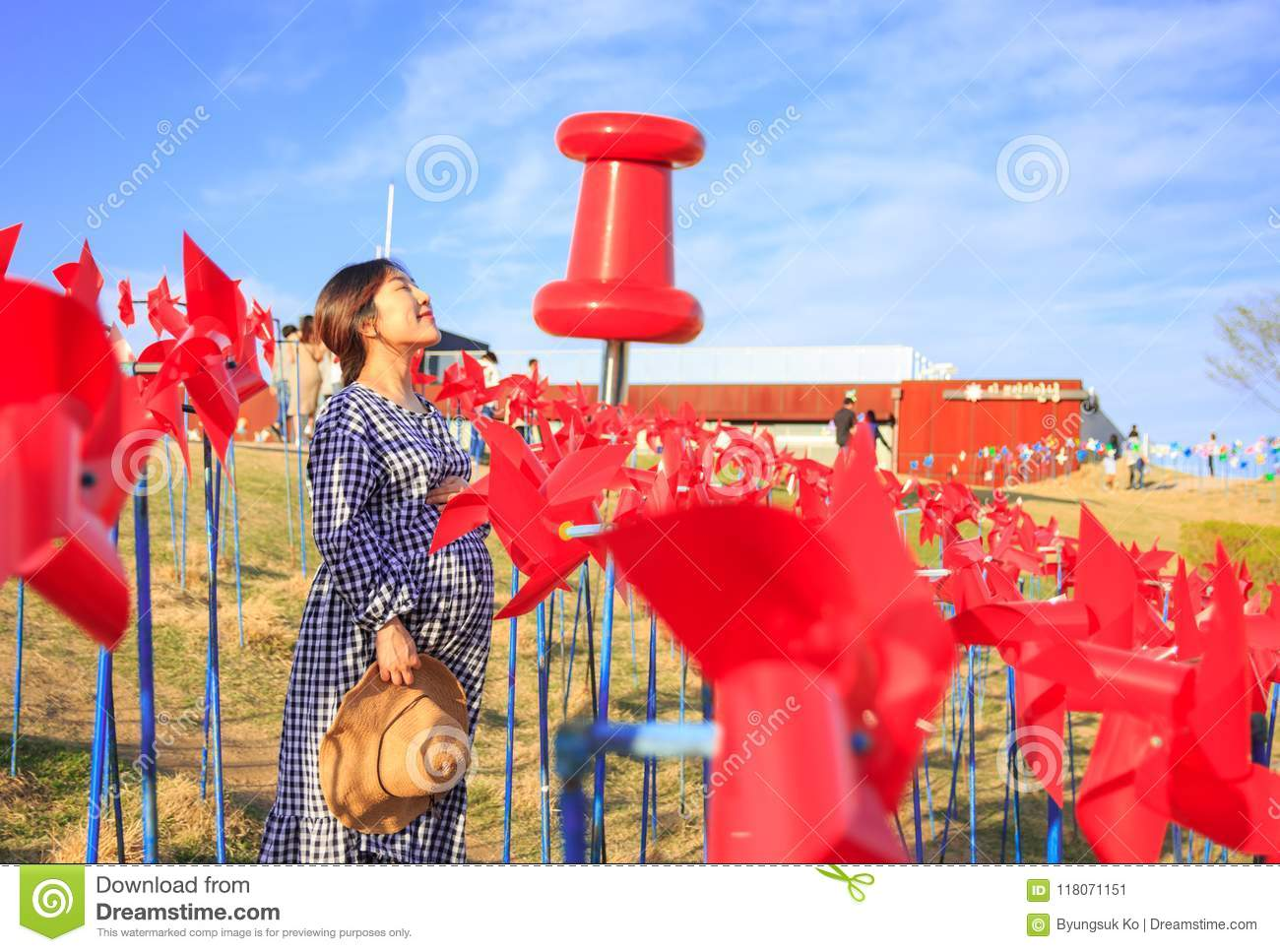 Asian pregnant woman in the middle of red pinwheel