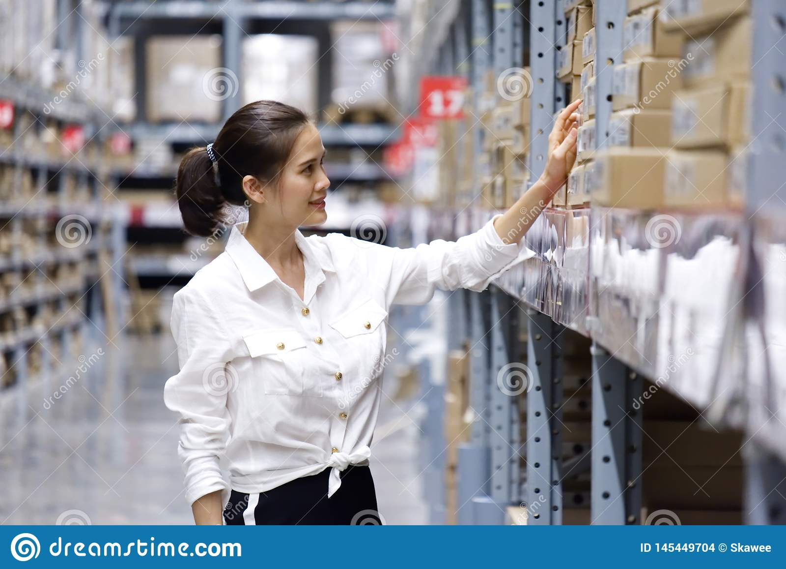 Asian pretty customer searching products in store warehouse. The girl using her hand point to the label to check the number at the