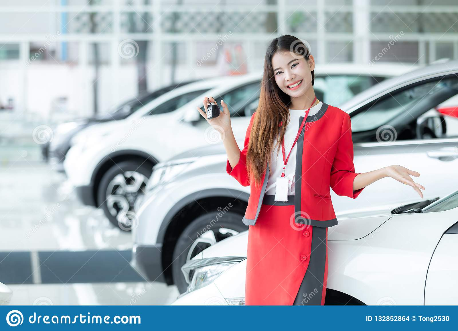 Asian saleswoman giving car key over auto show background, auto