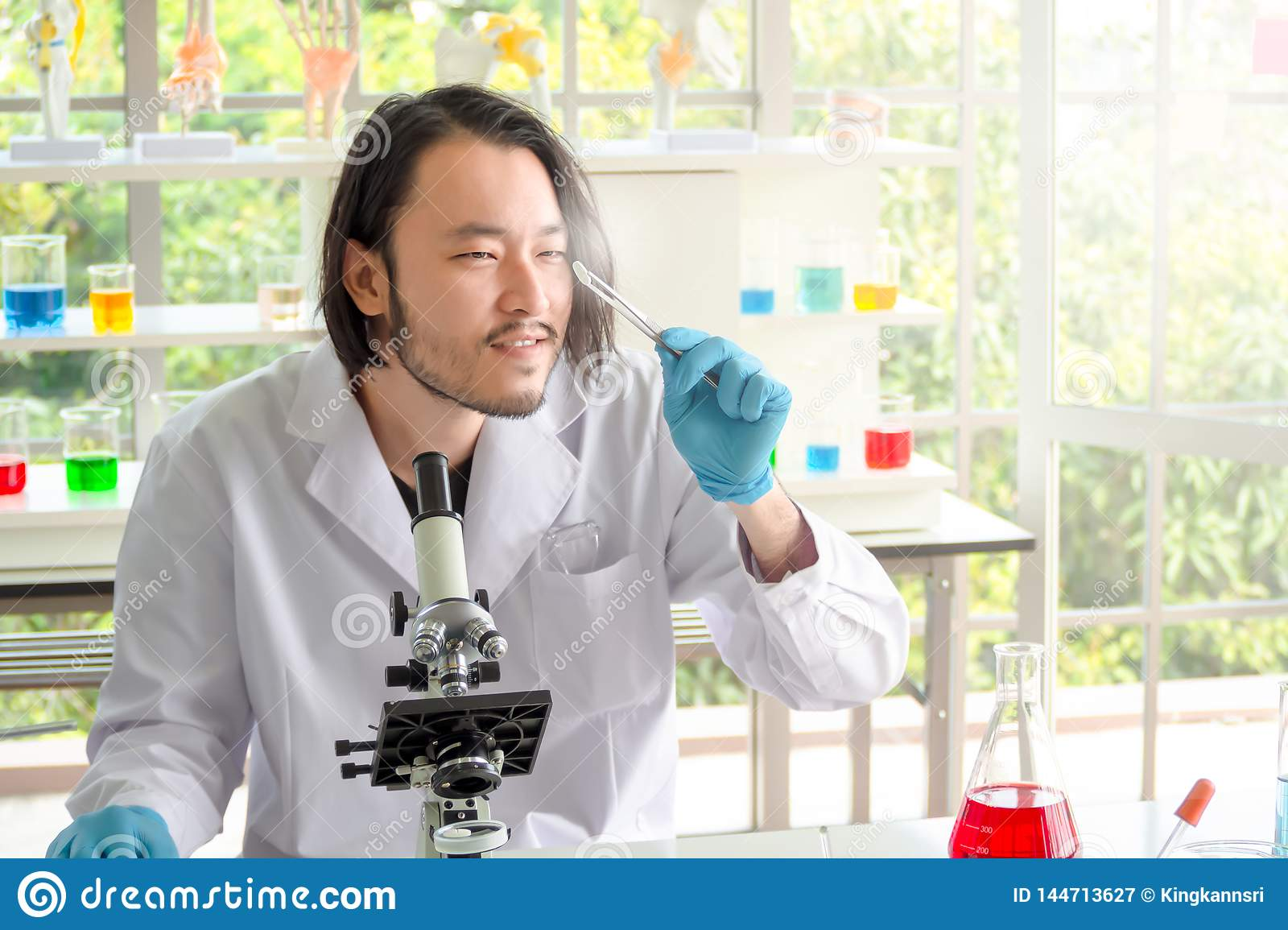 Asian  scientist or chemist  looking at a pill in laboratory, The young man testing medicine in medical experiment. Healthcare,