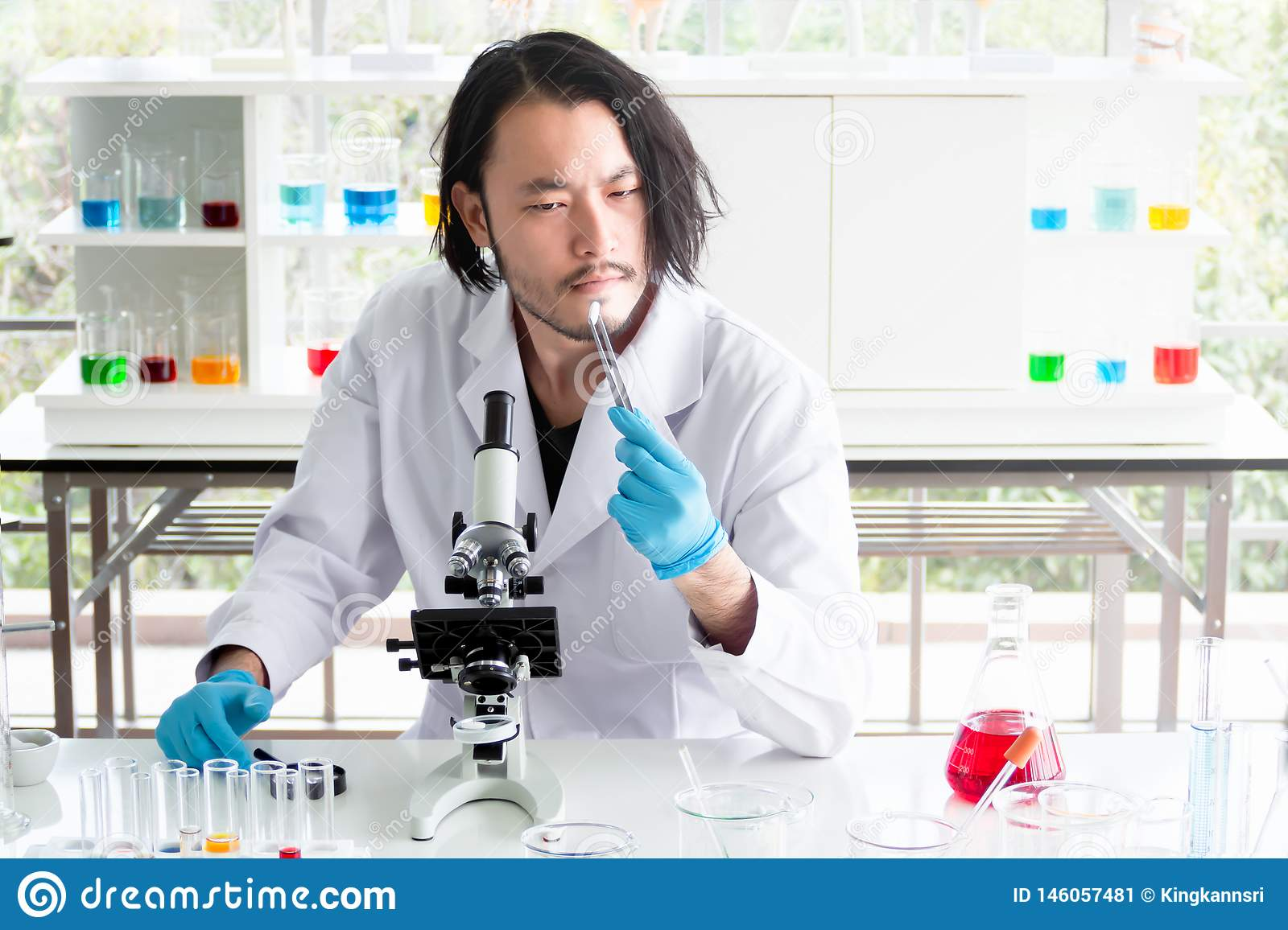 Asian  scientist or chemist  looking at a tablet in laboratory, The young man testing medicine in medical experiment. Healthcare,