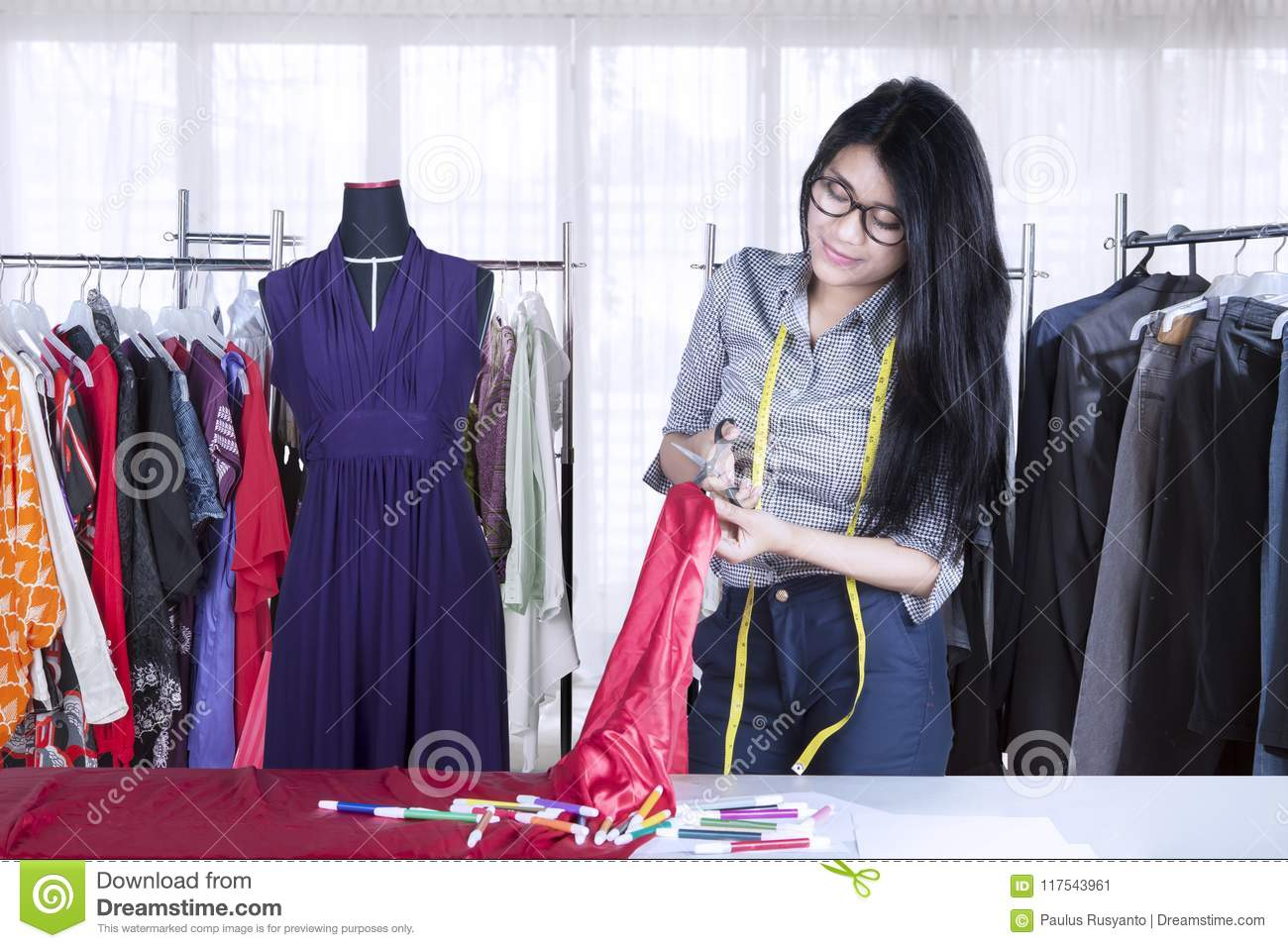 Asian seamstress cutting a fabric in the workplace