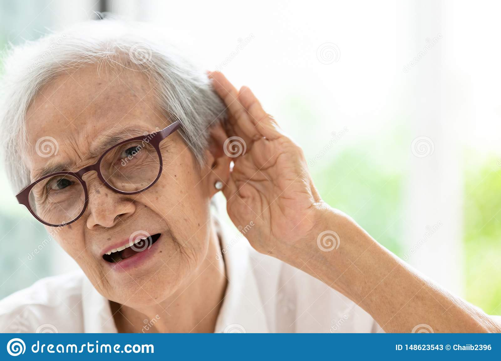 Asian senior woman listening by hand's up to the ear,having difficulty in hearing,elderly woman hard to hear,wear glasses with