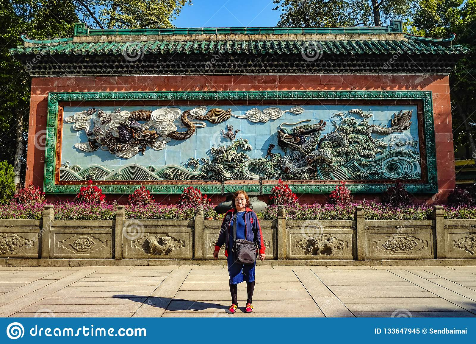 Asian senior women with Two chinese Dragon on the Blue wall in `The Ancestral temple `