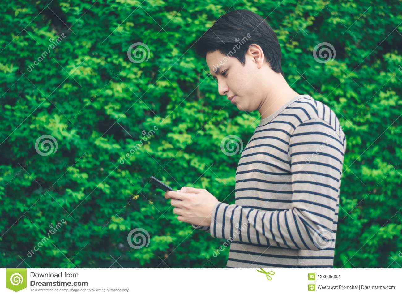 Asian man standing and using smartphone