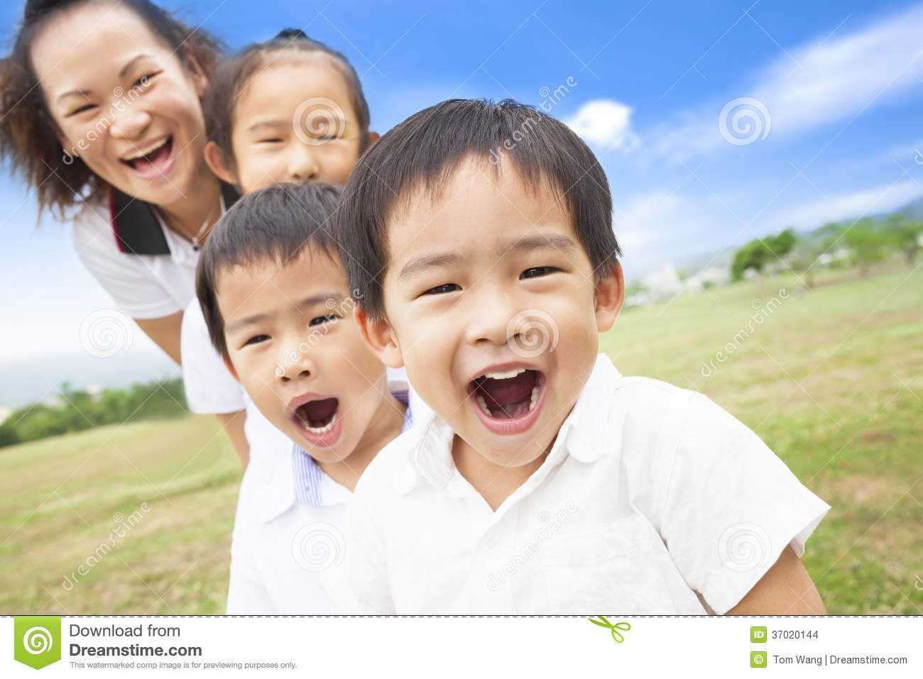 Asian smiling family playing on meadow and sunny day