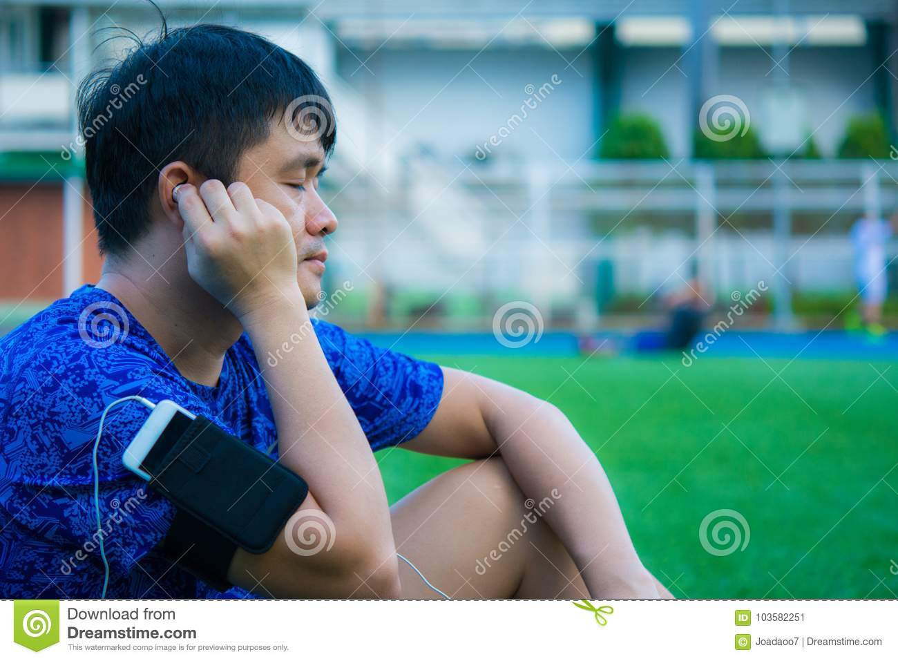 Asian sport man is listening his favorite song by smart pohne th