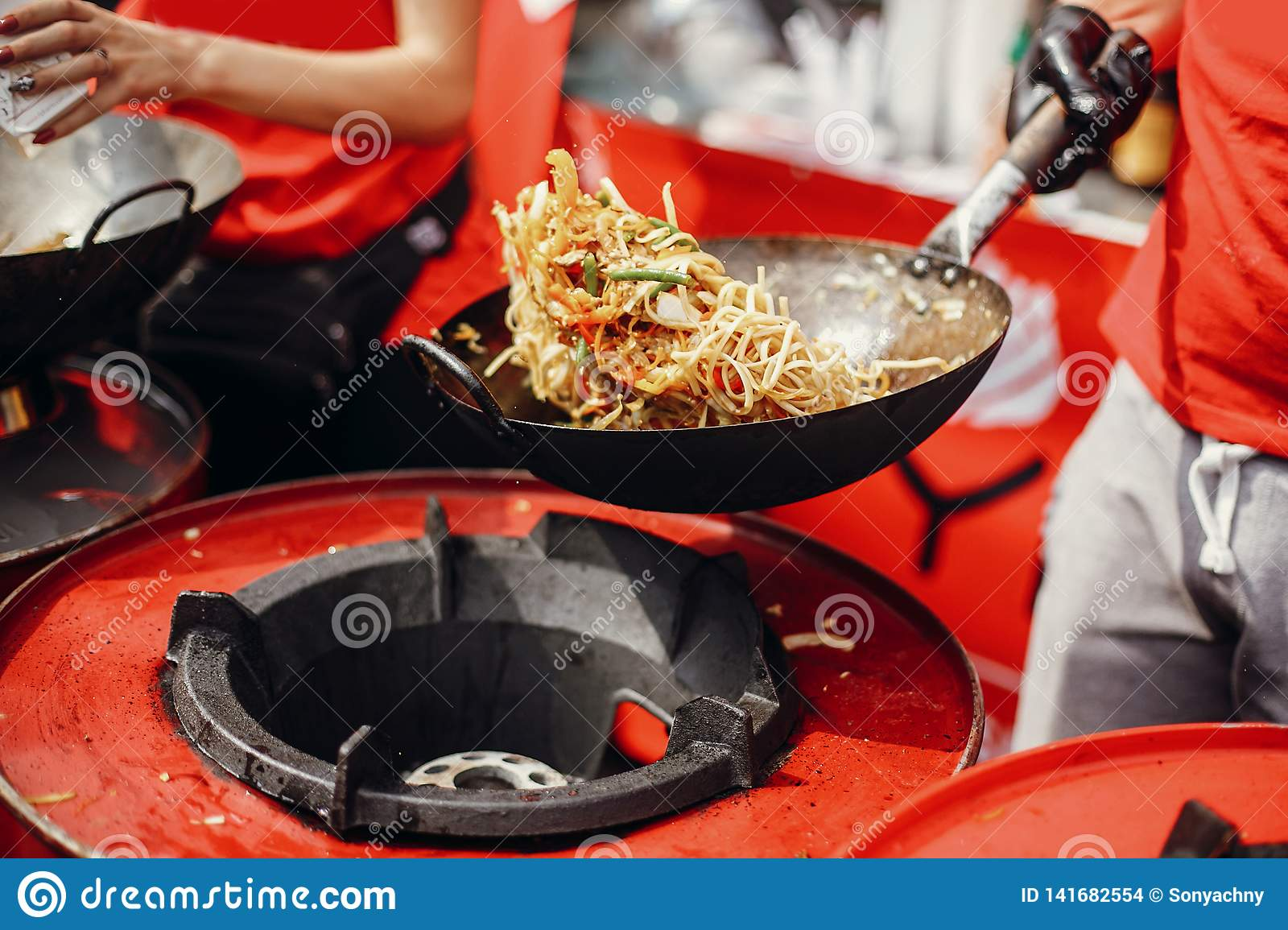 Asian street food festival in city. Chef cooking noodles and vegetables in a pan on fire. Fried chinese japanese noodles with