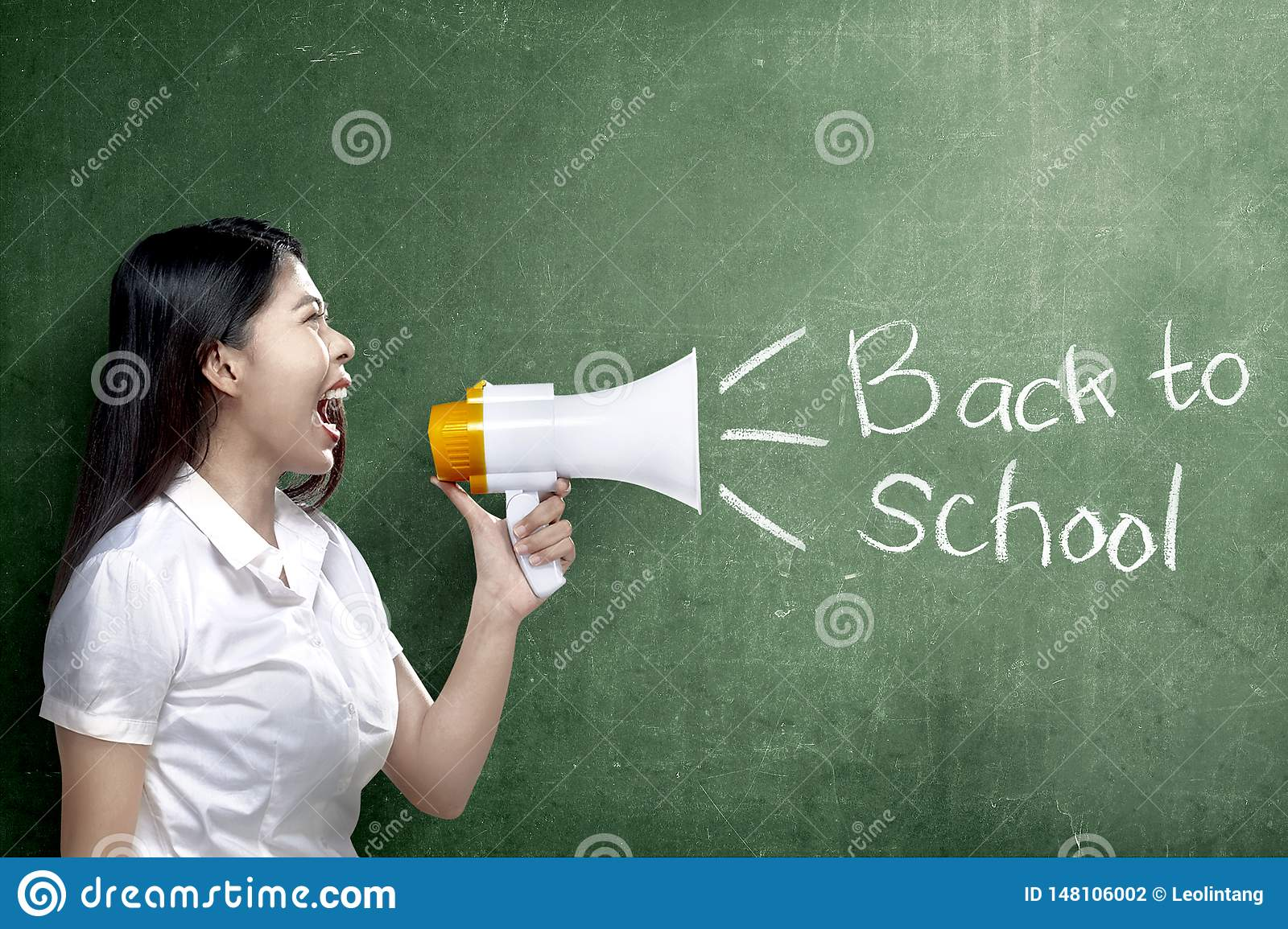 Asian teacher woman using megaphone to notify for go back to school with chalkboard background