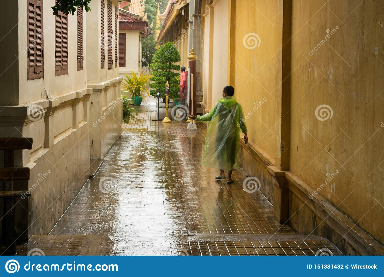 Asian teen waiting for the monsoon rain to stop