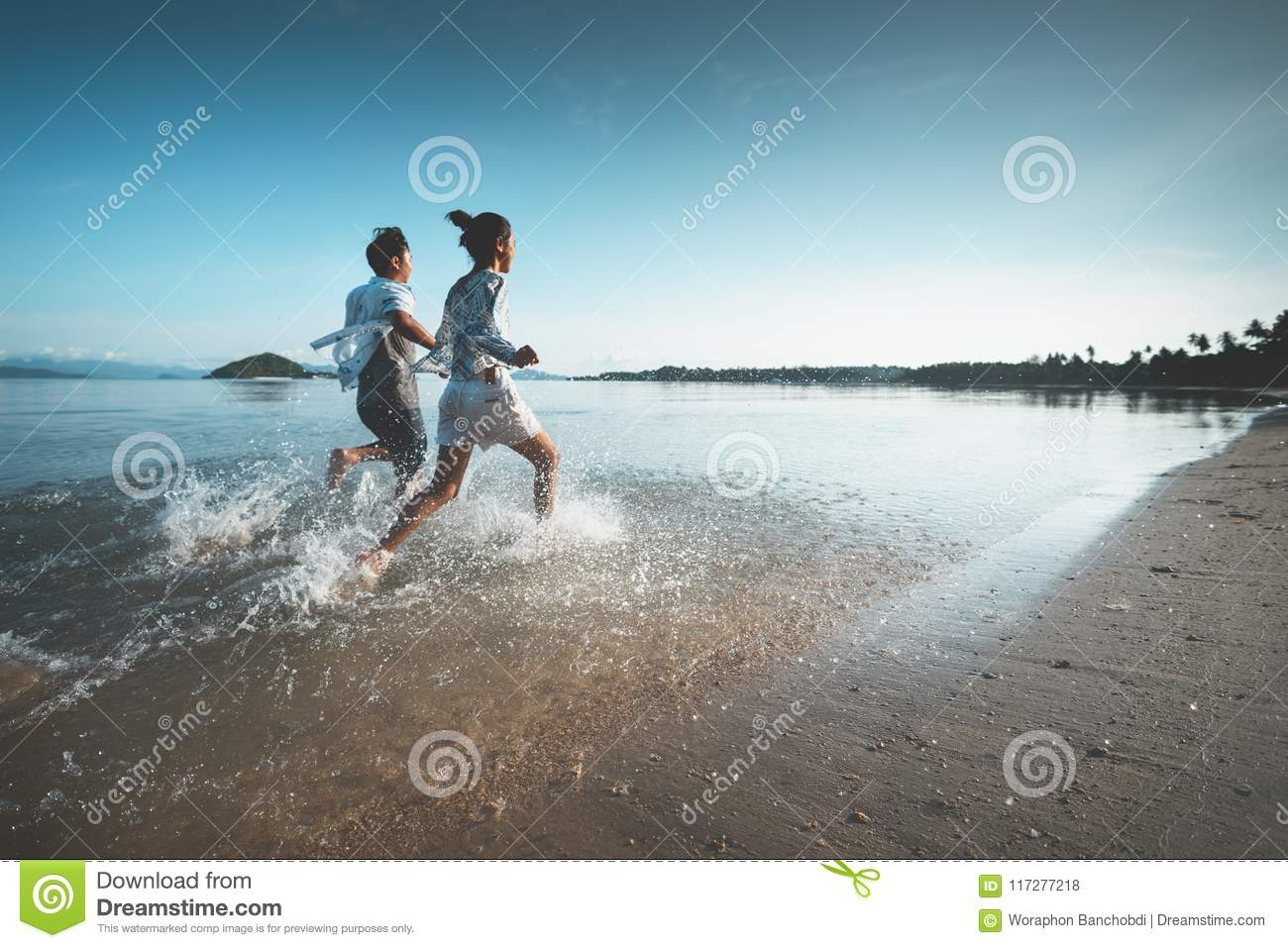 Asian teenage girl and boy running on the beach