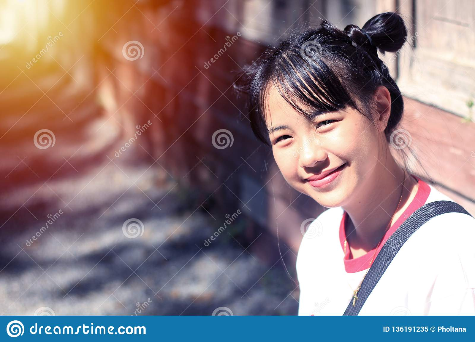 Asian teenage girls do hair tie, two pacifiers are smiling.