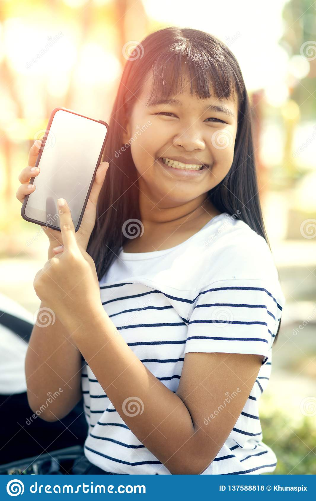 Asian teenager show white screen of smart phone screen and toothy smiling face happiness emotion