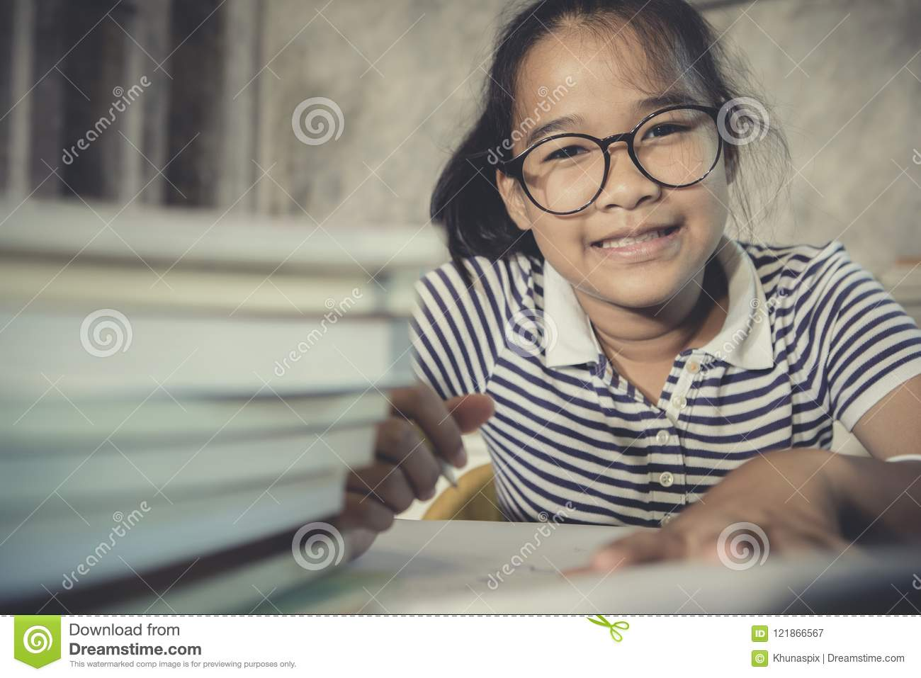 Asian teenager wearing eye glasses doing home work with stack of