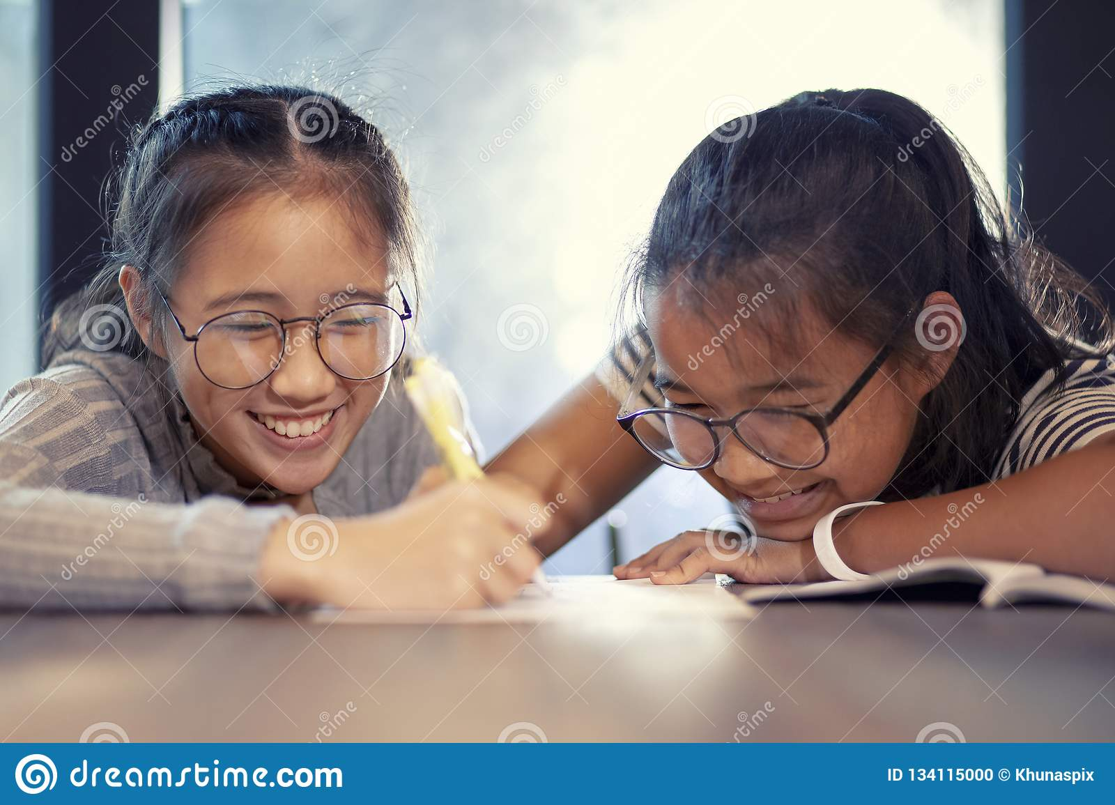 Asian teenager writing by pen on white paper and toothy smiling with happiness emotion